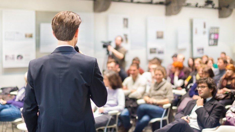 bigstock-Speaker-Talking-at-Business-Co-930x526