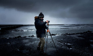guy using a camera on tripod in arctic setting